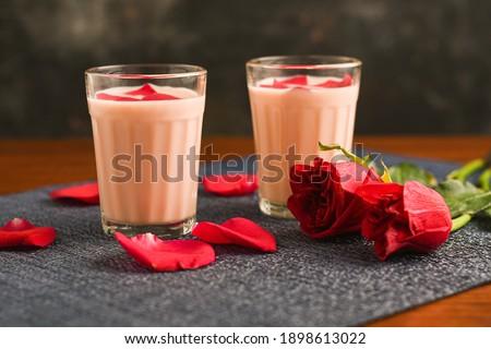 Rose milk , Rose shake , Gulab Shake with rose petals Indian valentines day drink with heart shaped red rose flowers Kerala. strawberry milk shake or Pink Tea , Gulabi Chai refreshment Kashmir India.