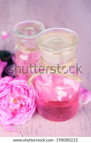 Rose oil in bottle on color wooden background