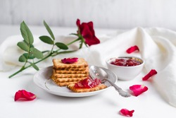 Rose petal jam with passionfruit with cookies on a white plate