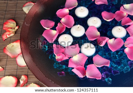 Rose petals and candles in water in vase close-up
