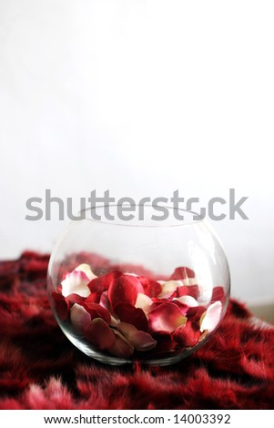 Rose petals in a glass bowl on a table - home interiors.