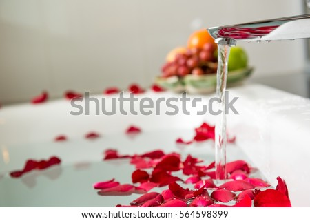 Rose petals put in bathtub for romantic bathroom in honeymoon suit.Arranged by interior designer for honeymoon couple. Scent of rose make relax. Spa shop put flowers in the tub with towels for lover. Foto stock ©