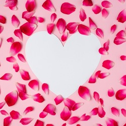 Rose petals with a white love shape copy space. Flat lay view.