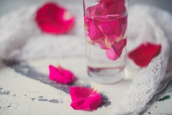 Rose pink water - water with petals of rose flowers in a transparent glass
