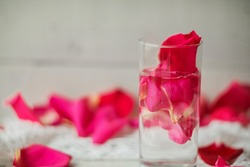 Rose pink water - water with petals of rose flowers in a transparent glass.