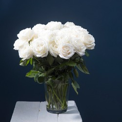 Rose Playa blanca. Bouquet of white roses in a glass vase on a beige table against a black wall. Copy space. A place for text.