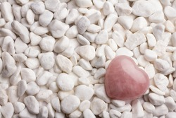 Rose quartz heart on pebbles.