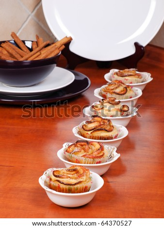 Rose shaped cookies from puff pastry, apples and cinnamon in the kitchen surroundings