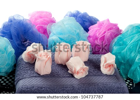 Rose shaped fragrance soap on purple towel with shower poufs against a white background.
