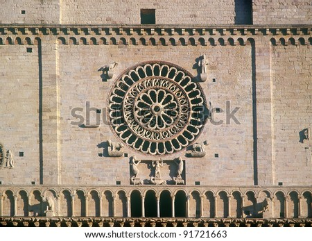 Rose window. St. Rufino cathedral. Assisi. Umbria. Italy - UNESCO World Heritage Site. The Romanesque facade is a typical example of the style found in 12th-century churches of Umbria.