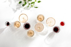Rose wine assortment, top-down view of various wine glasses full of rose and red wine, standing on a white table surface  reflecting soft sunshine rays
