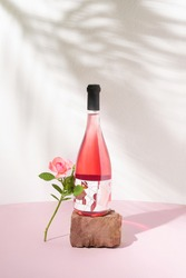 Rose wine bottle on red stone and one pink rose against white wall with summer shadows. Refreshing alcoholic summer drink or nature concept.