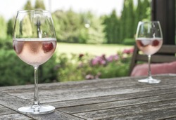 rose wine in glasses on wooden table at garden in a sunny day