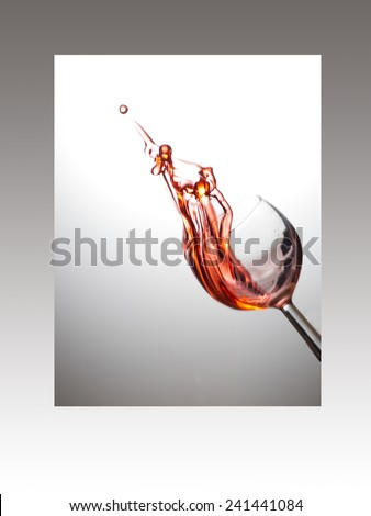 Rose wine splash caught midair. round bubble at point. White grey background.