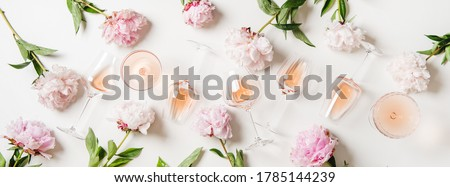 Rose wine variety layout. Flat-lay of rose wine in glasses and summer peony flowers over white background, top view. Summer drink for party, wine shop or wine tasting concept