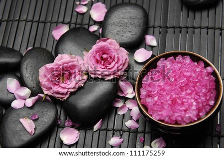 rose with spa salt in bowl and stones on bamboo mat