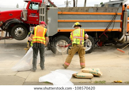 ROSEBURG, OR - JULY 20: Fire fighters cleaning up at a four vehicle accident involving two large trucks resulted in a single injury and a diesel fuel spill. July 20, 2012 in Roseburg Oregon