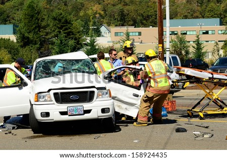ROSEBURG OR SEPTEMBER 11 2013 Firefighters extricate victims of a two vehicle t-bone accident at an intersection resulted in major injuries in Roseburg Oregon on September 11 2013