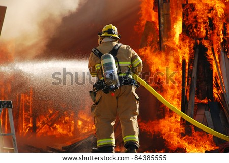 ROSEBURG, OR - SEPTEMBER 03: Single fire fighter spraying a straight steam into a fully involved shop fire off of Breezy Lane, September 03, 2011 in Roseburg, OR