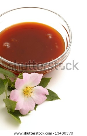 Rosehip jam in glass bowl and rosehip flower