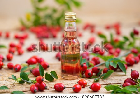 Rosehip oil in glass bottle with berries around from close up. Raw liquid from little red fruit on wooden desk. Small jar of drink from seeds. Stock photo ©