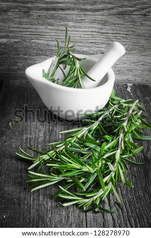 Rosemary branch in a white mortar on a wooden background