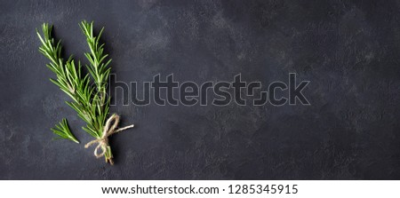 Rosemary herbs on dark stone background. Copy space for menu or recipe. Flat Lay.