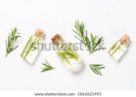 Rosemary oil. Bottle glass with rosemary essential oil and fresh rosemary twig on white background. Top view.
