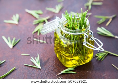 Rosemary oil. Rosemary essential oil jar glass bottle and branches of plant rosemary with flowers on rustic background. #509029621
