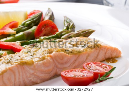 Rosemary roasted salmon served with asparagus, cherry tomatoes, red bell pepper topped by mustard rosemary sauce and glass of ice water for healthy style dinner