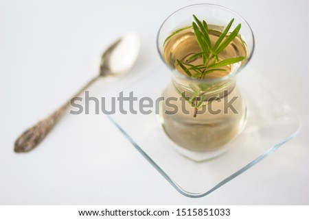 Rosemary tea in Armudu glass with branch of rosemary in it and spoon on the table on the white background Photo stock ©