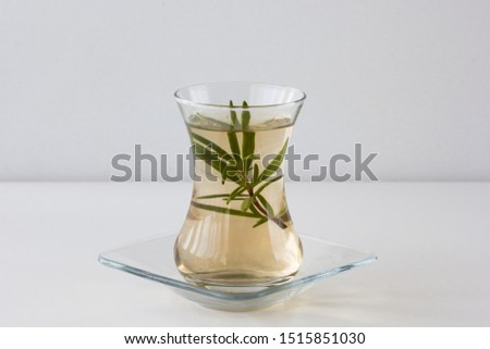 Rosemary tea in Armudu glass with branch of rosemary in it on the table on white background Photo stock ©