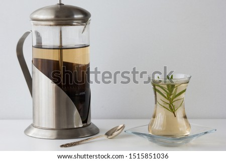 Rosemary tea in Armudu glass with branch of rosemary in it, teapot and spoon on the table on the white background Photo stock ©