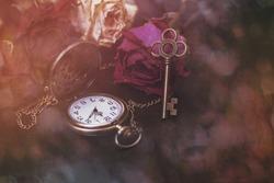 Roses, a pocket watch and an old key. Vintage Wonderland background. Soft selective focus, toning