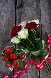 roses and strawberries on dar woodensurface
