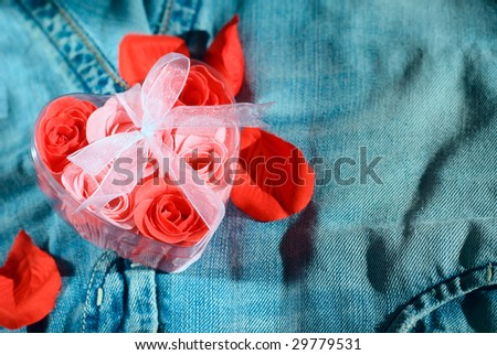 Roses in a gift box in shape of heart on jeans fabric