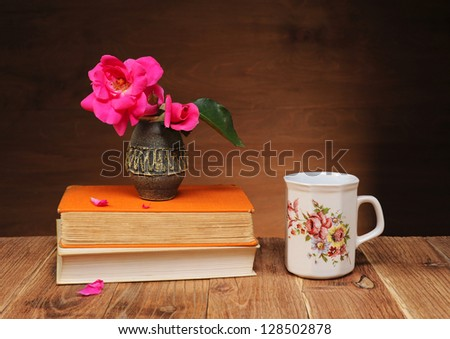 Roses in a vase on the table and books