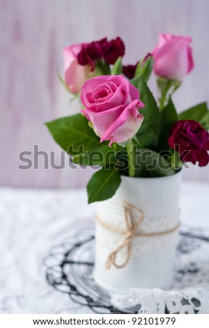 Roses in a white tin can with twine jute
