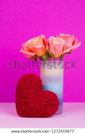 Roses in vase and decorative heart. Red heart of thread and orange flowers. St. Valentine's Day #1272459877