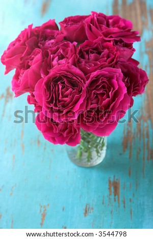 Roses in vase on rustic table