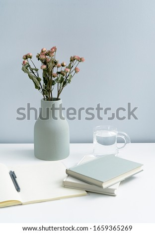 Roses in vase on white table top. Books notebook and plain vase on white desktop. Book notebook in minimalist home. Roses in vase on white table top