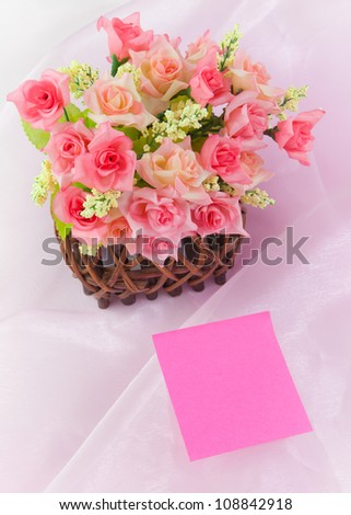 Roses in wood basket on fabric pink background - stock photo