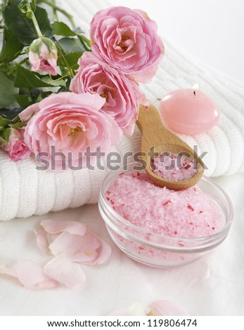roses lying on towel with salt in bowl and candle on soft towel - stock photo