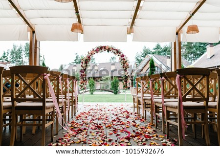 Roses petals scattered on the road. wedding decor. Wooden chairs in the backyard banquet area. Arch for wedding ceremony a is decorated with flowers and greens, greenery.