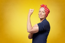 Rosie Riveter concept: proud senior woman with red headscarf, flexing her muscles, copy space, yellow background
