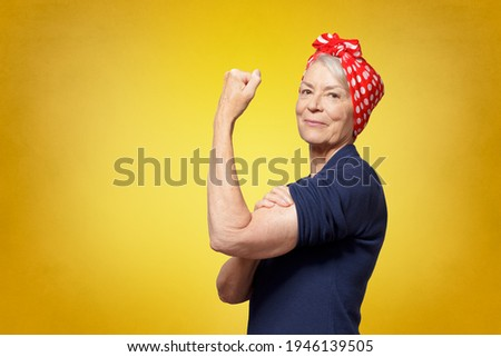 Rosie Riveter concept: proud senior woman with red headscarf, flexing her muscles, copy space, yellow background Stockfoto ©