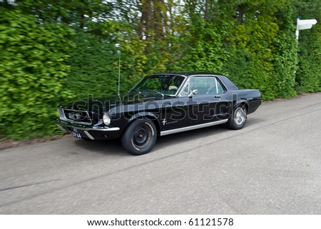 ROSMALEN, THE NETHERLANDS - MAY 16: Black 1967 Ford Mustang HTP Coupe arriving on the Rock Around the Jukebox Open Air event on May 16, 2010 in Autotron Rosmalen in Holland.