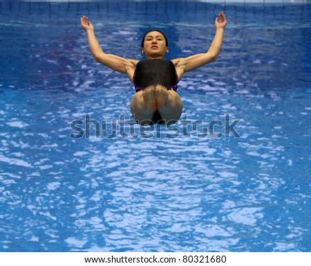 """ROSTOCK, GERMANY - MAY 29: Leong Mun Yee (MAS) during a warming up jump on May 29, 2011 in the scope of the """"56th International Diver's Day"""" at the site of the Neptun swimming pool in Rostock, Germany."""