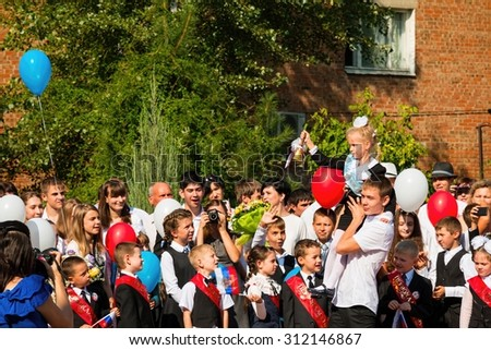 Rostov - on - Don, Russia - September 1, 2015: School line is in schoolyard with first-grade pupils and teacher. Children go back to school. The Knowledge Day in Russia, first day of school.