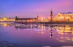 Rostral columns on the Strelka of Vasilyevsky Island with a reflection in the Neva River in St. Petersburg on a pink winter morning
